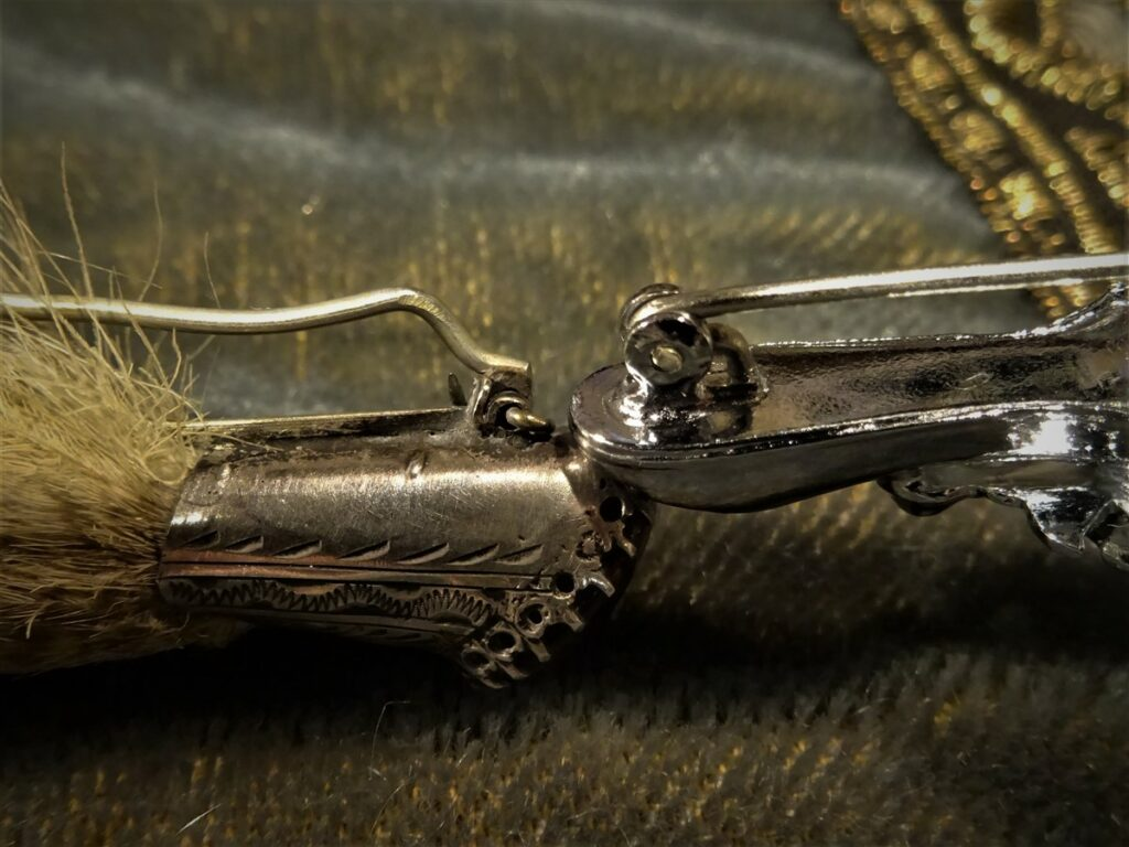 Two grouse claw pins. A Victorian clasp on the left and a modern clasp on the right